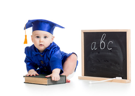 Baby in academician clothes  with book at chalkboard photo