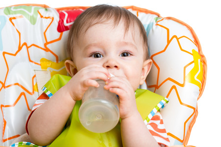 high chair: happy baby drinking from bottle sitting in high chair Stock Photo