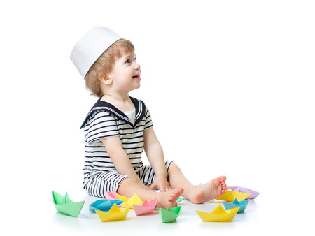 mariner: Cute baby boy with sailor hat  playing with paper boats