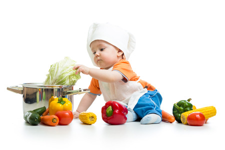 baby chef with healthy  food vegetables and pan photo