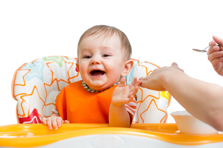 highchair: baby sitting in highchair and eating with a spoon Stock Photo