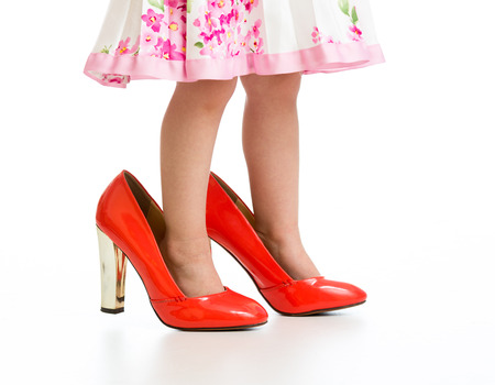 Little girl in big red shoes isolated on white