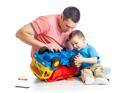 plastic toys: kid boy and his dad repair toy trunk