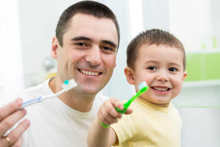 father and child son brushing teeth in bathroom photo