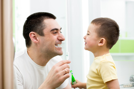 cleaning bathroom: child boy and his dad cleaning teeth in bathroom