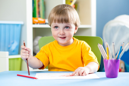 kid boy drawing with pencils indoors photo