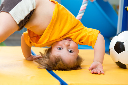 baby standing upside down on gym mat photo