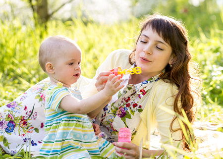 mother and kid girl having fun outdoors photo