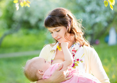 young mother breast feeding her baby girl outdoors photo