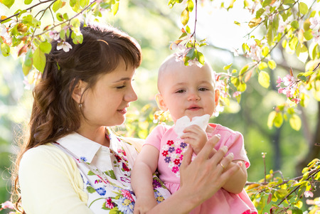 Allergy. Mother and baby blowing nose outdoors photo
