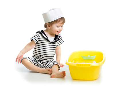 Cute baby boy with sailor clothes playing with paper boats photo