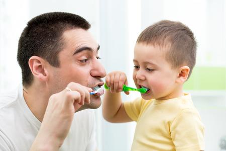 子供の少年と彼のお父さんがバスルームで歯を磨く