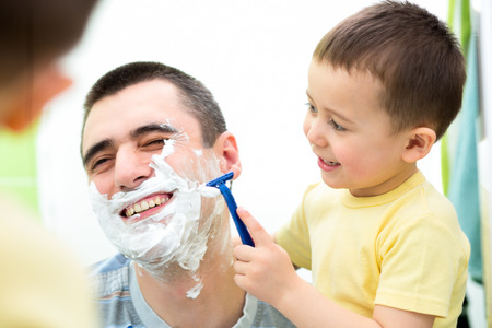 playful kid and dad shaving together at home bathroom photo