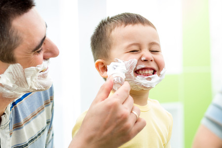 playful kid and father shaving together at home bathroom photo