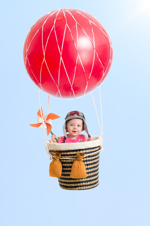cheerful kid on hot air balloon in the sky photo