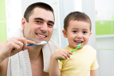 father and child boy brushing teeth before going to bed photo