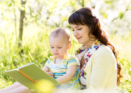 happy mother reading a book to child outdoors photo
