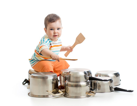 young boy using wooden spoons to bang pans drumset photo