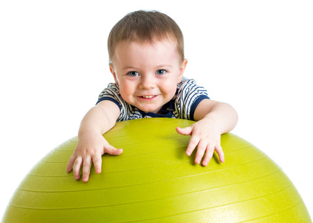 playschool: kid girl doing fitness exercise with fitness ball