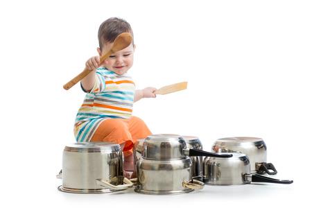 木製のスプーンを使用して鍋ドラムセットを強打する男の子 写真素材