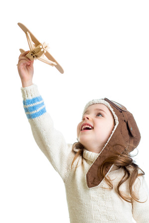 child girl dressed pilot helmet and playing with wooden airplane toy photo