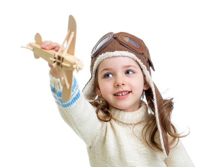 child dressed as pilot and playing with wooden airplane toy isolated on white background photo
