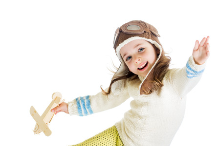 funny kid dressed as pilot and playing with wooden airplane toy isolated on white background photo