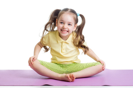 Cheerful kid girl doing exercises on fitness mat photo