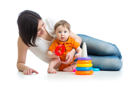 kid boy and mother play together with pyramid toy photo