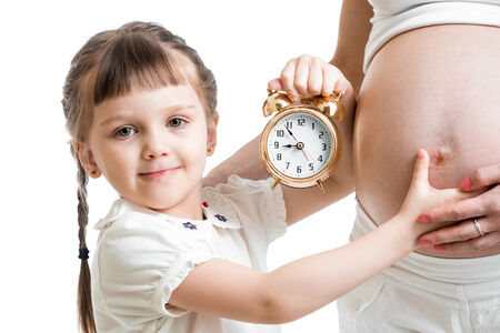 kid with an alarm clock and pregnant woman belly photo