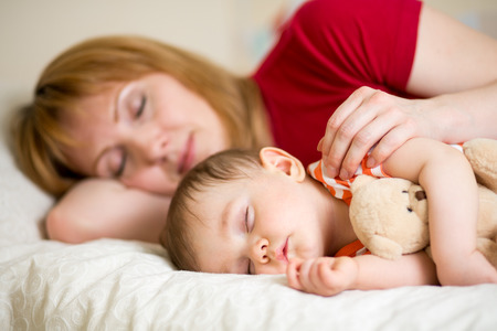 parental love: mother and her baby sleeping together