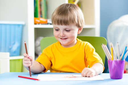 kid boy drawing with pencils at home photo