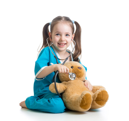 Adorable niño con ropa de médico examinar el oso de peluche de juguete sobre blanco Foto de archivo