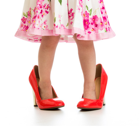 Kid girl in big red shoes isolated on white photo