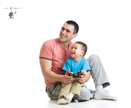 Kid boy and dad playing with RC helicopter toy photo