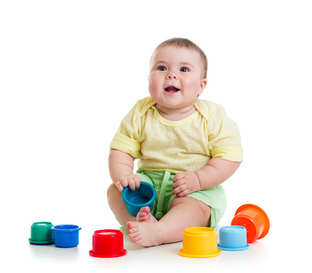 Cute baby girl playing with toys while sitting on floor photo