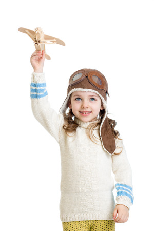 kid girl dressed pilot helmet and playing with wooden airplane toy photo