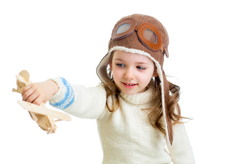 smiling child dressed pilot and playing with wooden airplane toy photo