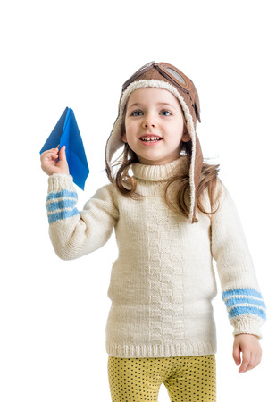 child girl dressed as pilot and playing with paper airplane isolated on white background photo