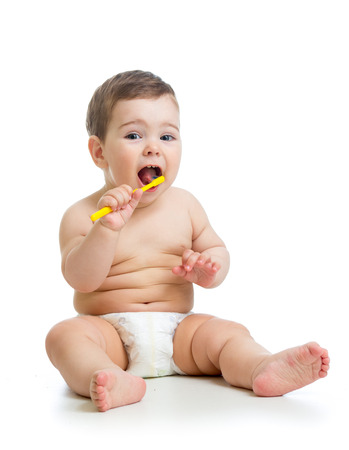 baby boy cleaning teeth and smiling, isolated on white background photo