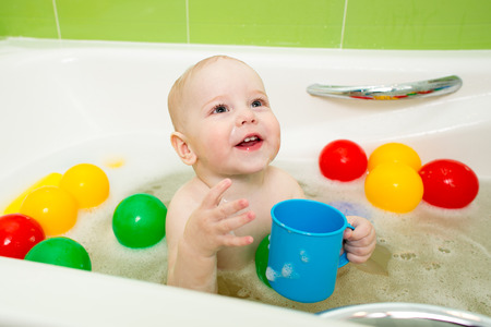 happy kid boy taking bath and playing with toys photo