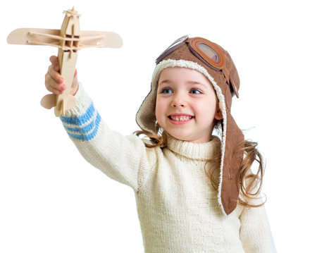 happy child dressed pilot and playing with wooden airplane toy photo