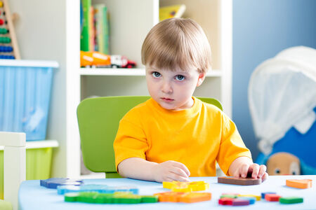 day care: child playing with puzzle toy indoor Stock Photo