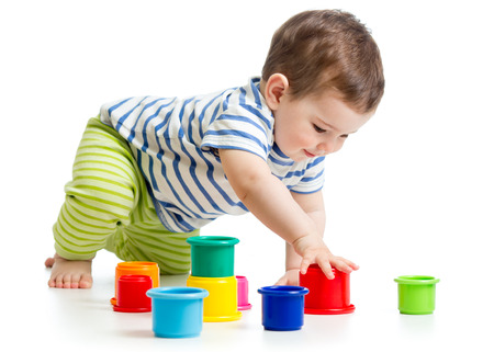 toddler boy playing with cup toys photo