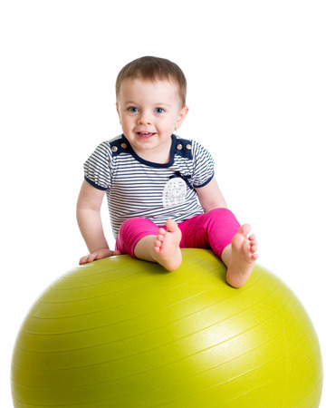 exhilarated: kid girl doing fitness exercise with fitness ball