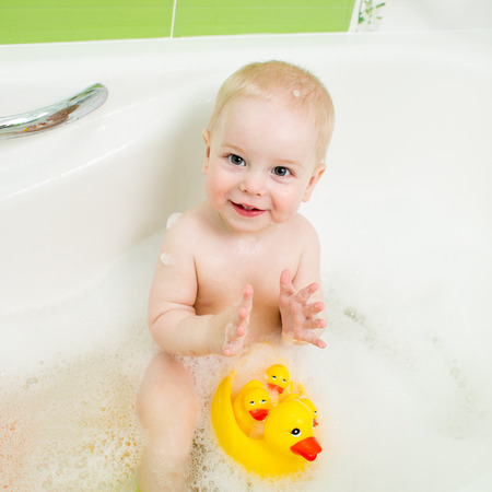 happy kid boy bathing  and playing with toys photo