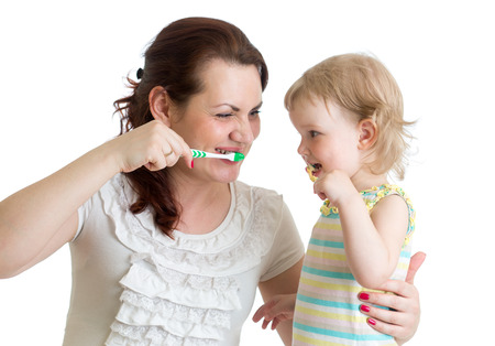 child with mom brushing teeth photo