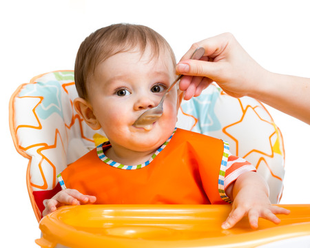kasha: baby boy feeding with a spoon Stock Photo