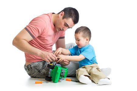 kind jongen en zijn vader reparatie speelgoedauto Stockfoto