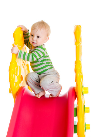 toddler boy playing on the slide photo